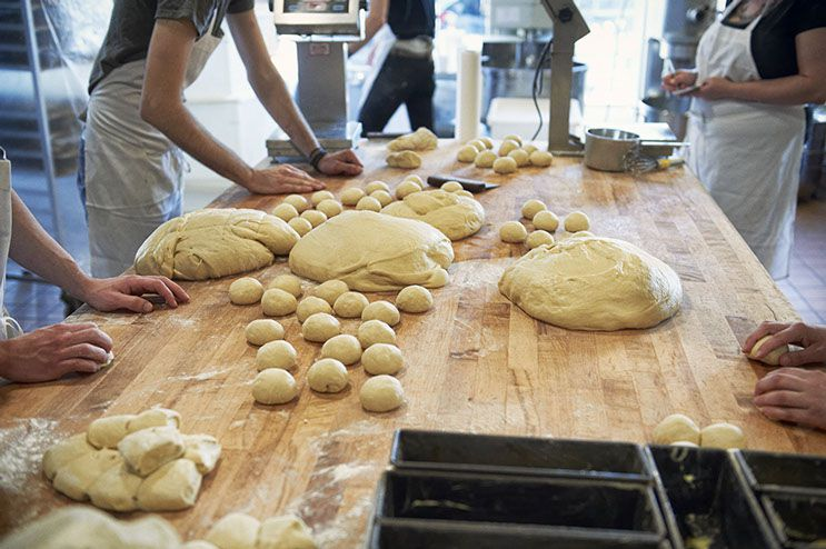 Workers stand around a wooden counter prepping dough balls