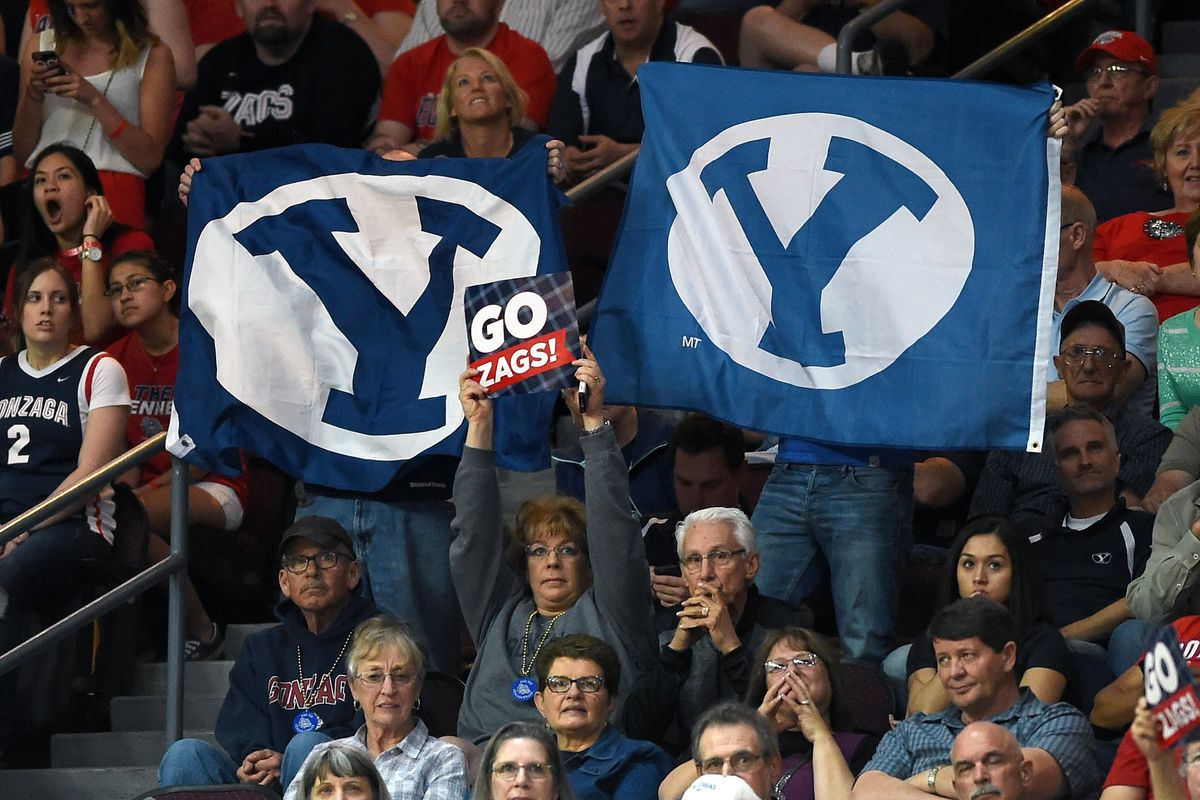 A Gonzaga fan holds up a sign between two BYU logos at the 2015 WCC Tournament in Las Vegas.