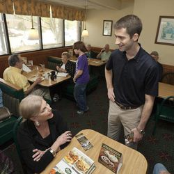 In this photo taken March 19, 2012, Republican Congressional candidate Tom Cotton, standing, greets people in a Hot Springs, Ark., restaurant. Cotton and one other Republican seeking the office in Arkansas' 4th District are veterans of the war in Afghanistan.