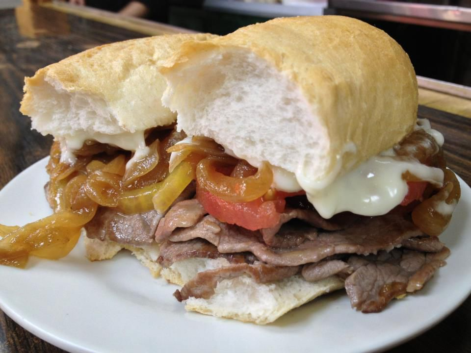 A sandwich stuffed with sliced beef, sautéed onions, tomato, and sauce on thick bread