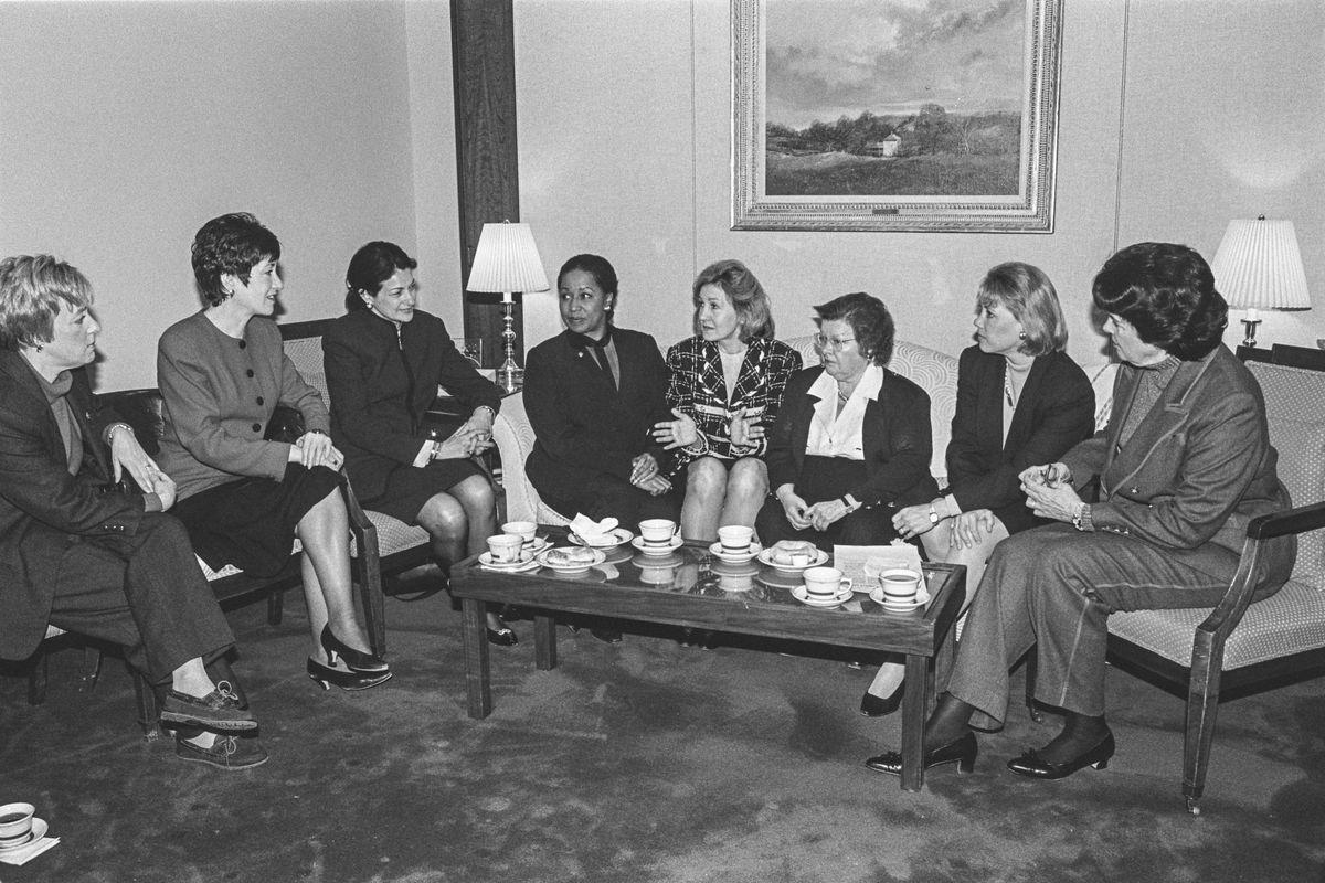 Women senators seated around a coffee table (left to right): Patty Murray, Susan Collins, Olympia Snowe, Carol Moseley Braun, Kay Bailey Hutchison, Barbara Mikulski, Mary Landrieu and Dianne Feinstein in 1997