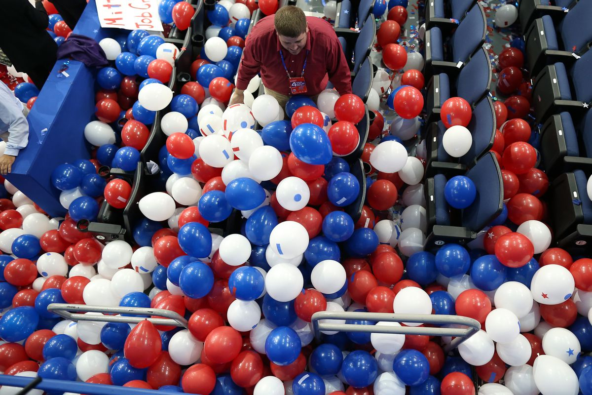 A person wades through balloons on the floor of a convention center.