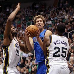 Dirk Nowitzki of the Dallas Mavericks, at center, is called for an offensive foul against Al Jefferson of the Utah Jazz, right during NBA basketball in Salt Lake City, Monday, Jan. 7, 2013. At left is Derrick Favors of the Utah Jazz.