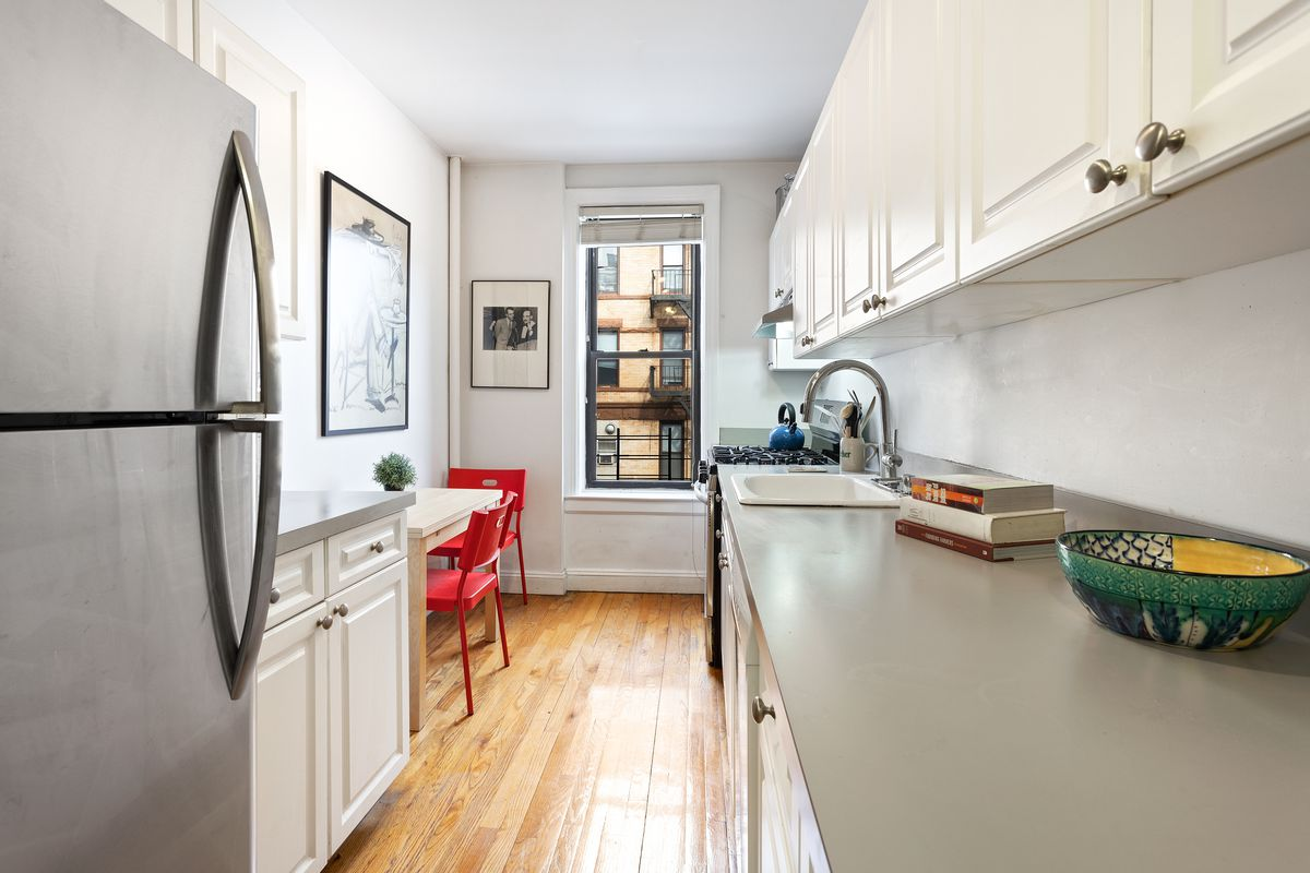 The galley kitchen features white cabinetry, gray countertops, stainless steel appliances, and a window.