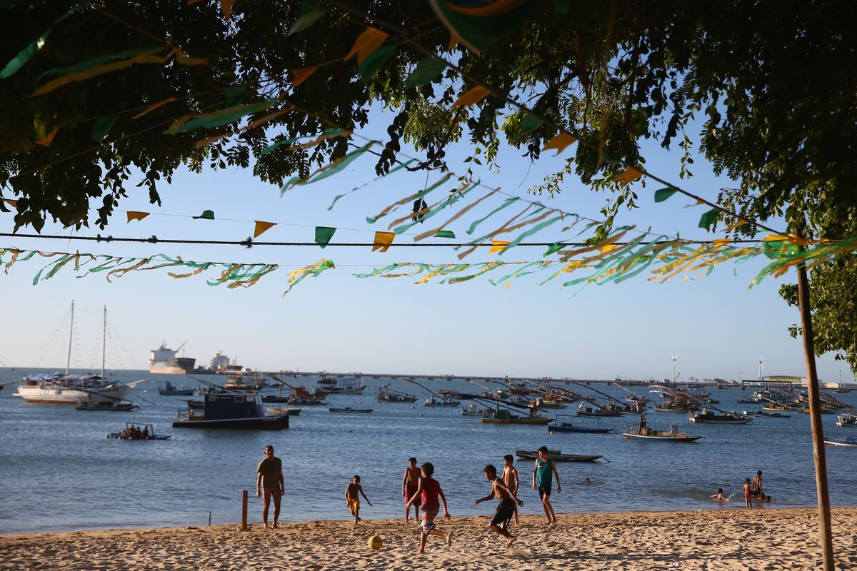 Locals play football at the Iracemar beach on June 22, 2014 in Fortaleza, Brazil.