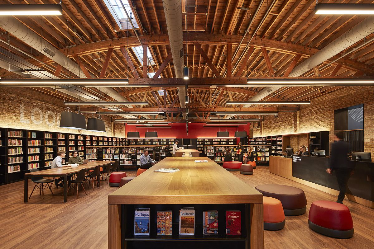 A long, rectangular library space beneath an arched wood timber ceiling. There are tables and chairs for reading the walls are lined with bookshelves.
