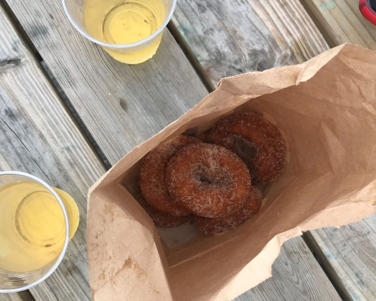 A paper bag of apple cider doughnuts and two cups of light yellow cider on a wooden table
