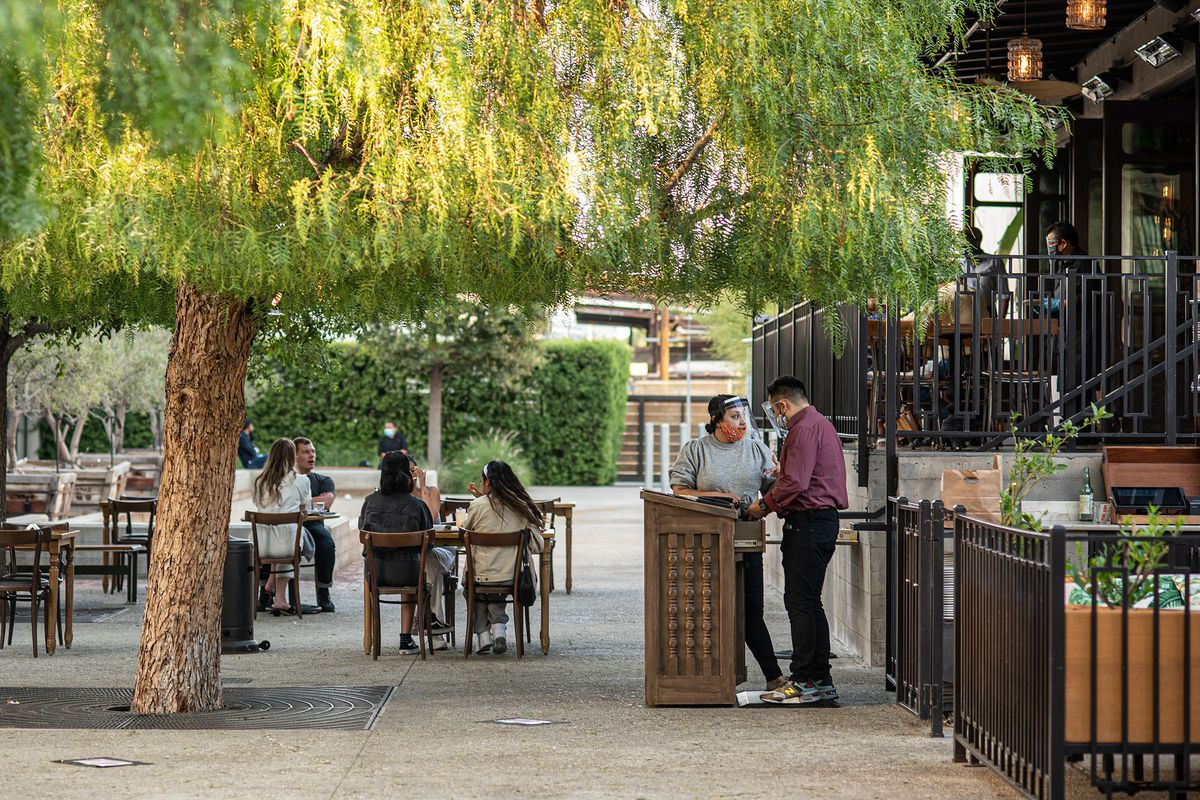 Workers and diners outside of Dama restaurant in Downtown Los Angeles covered by tree branches.