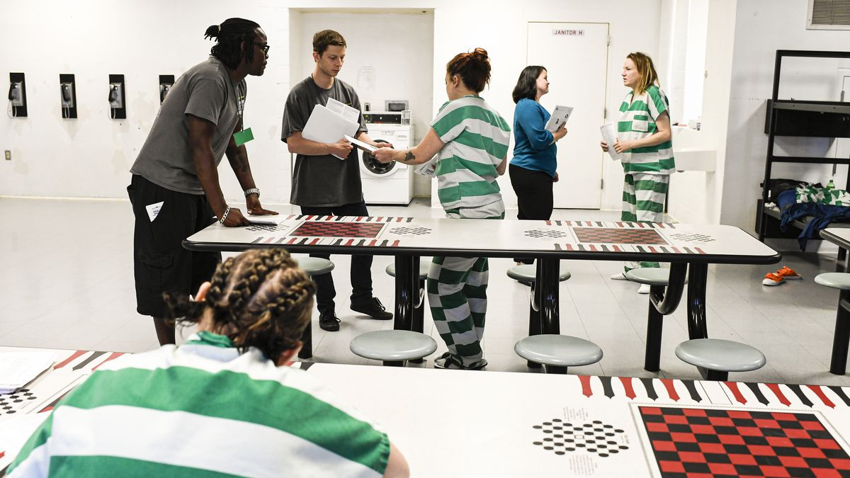 Several inmates in the communal room of a prison are handed voter registration forms by volunteers.