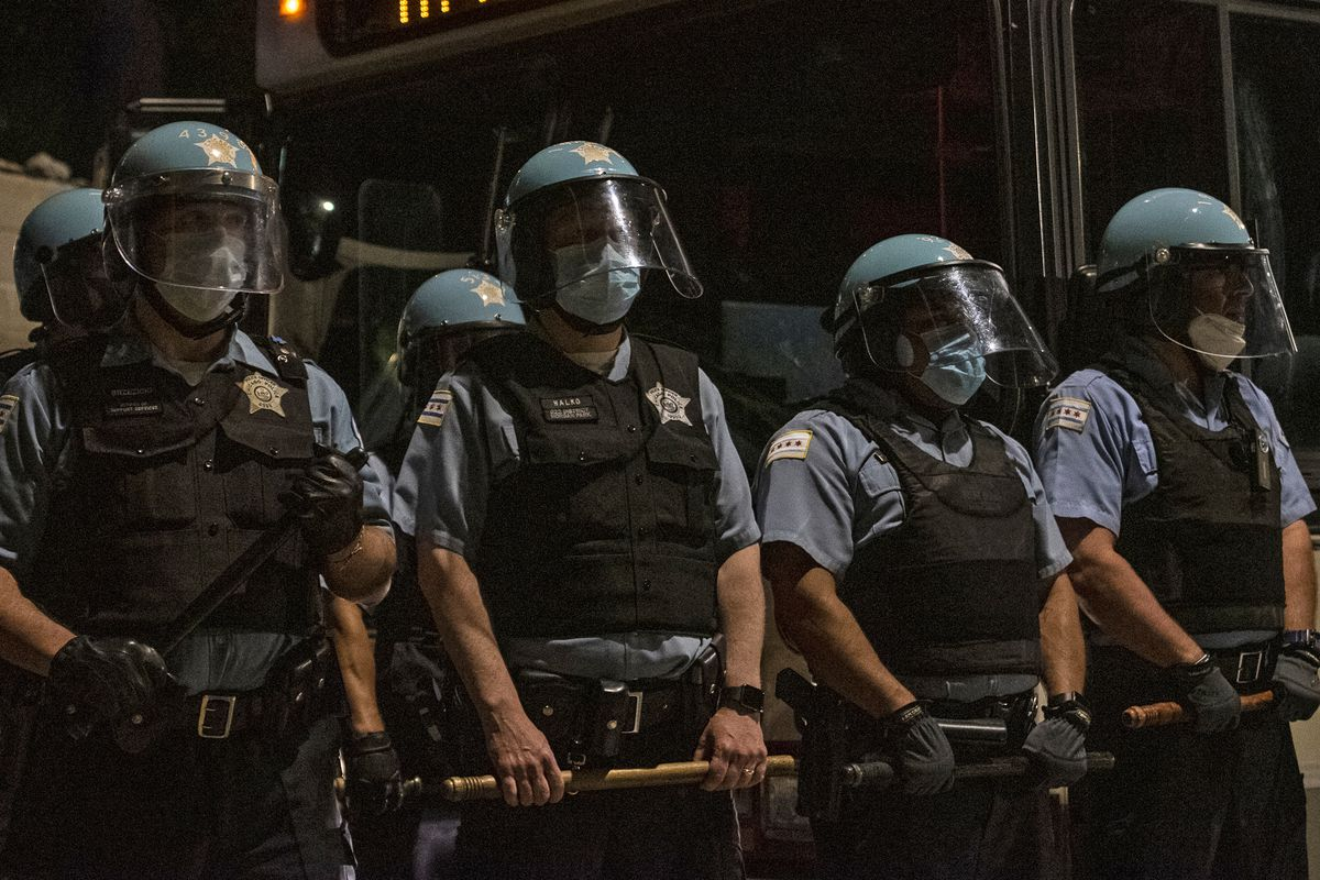 Chicago police officers block Michigan Avenue at 36th Street, using a CTA bus and their bodies while protesters march toward Chicago police headquarters on June 4, 2020.