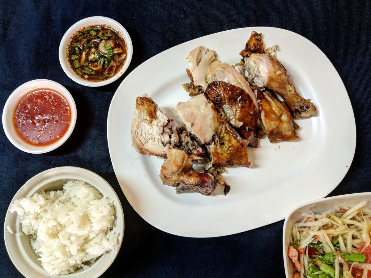A serving platter of roast chicken, beside a bowl of rice, side salad, and sauces on a dark table cloth