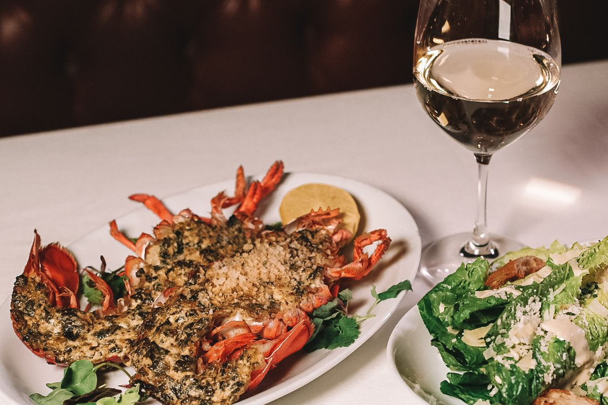 A lobster halved and a glass of wine