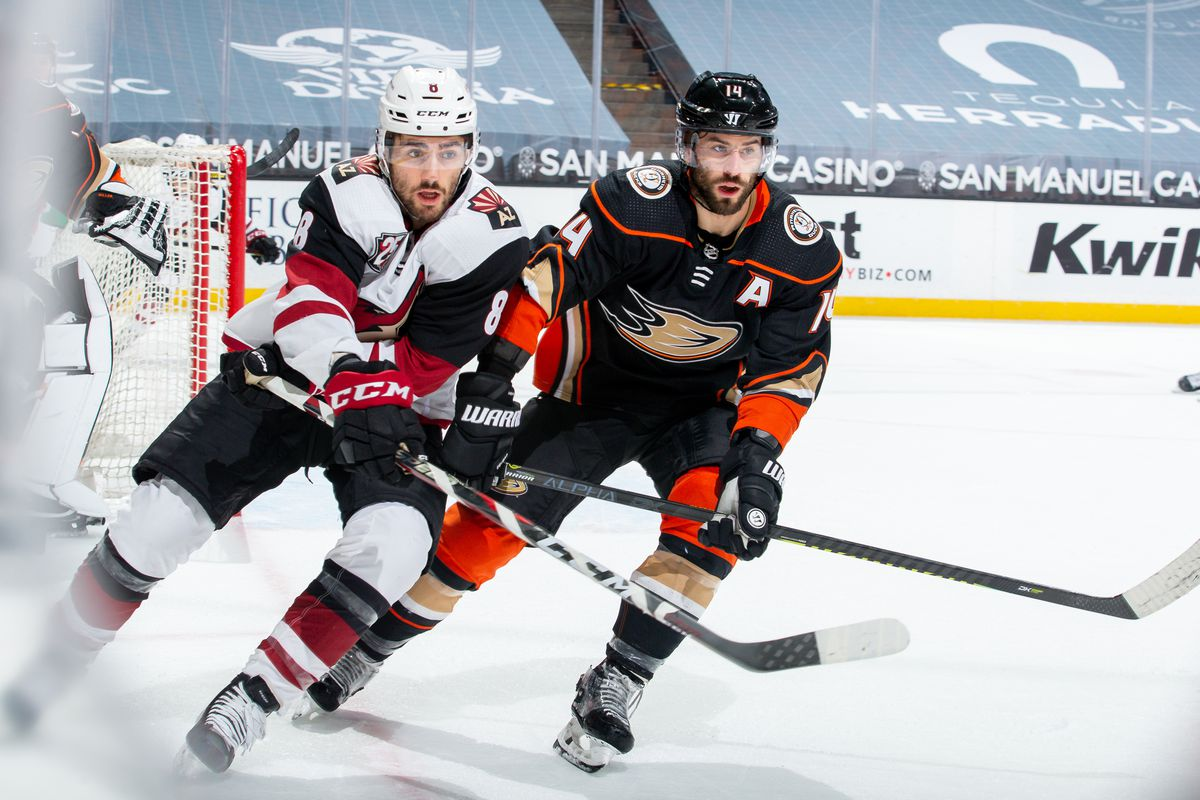 Nick Schmaltz #8 of the Arizona Coyotes and Adam Henrique #14 of the Anaheim Ducks race for the puck during the first period of the game at Honda Center on March 20, 2021 in Anaheim, California.