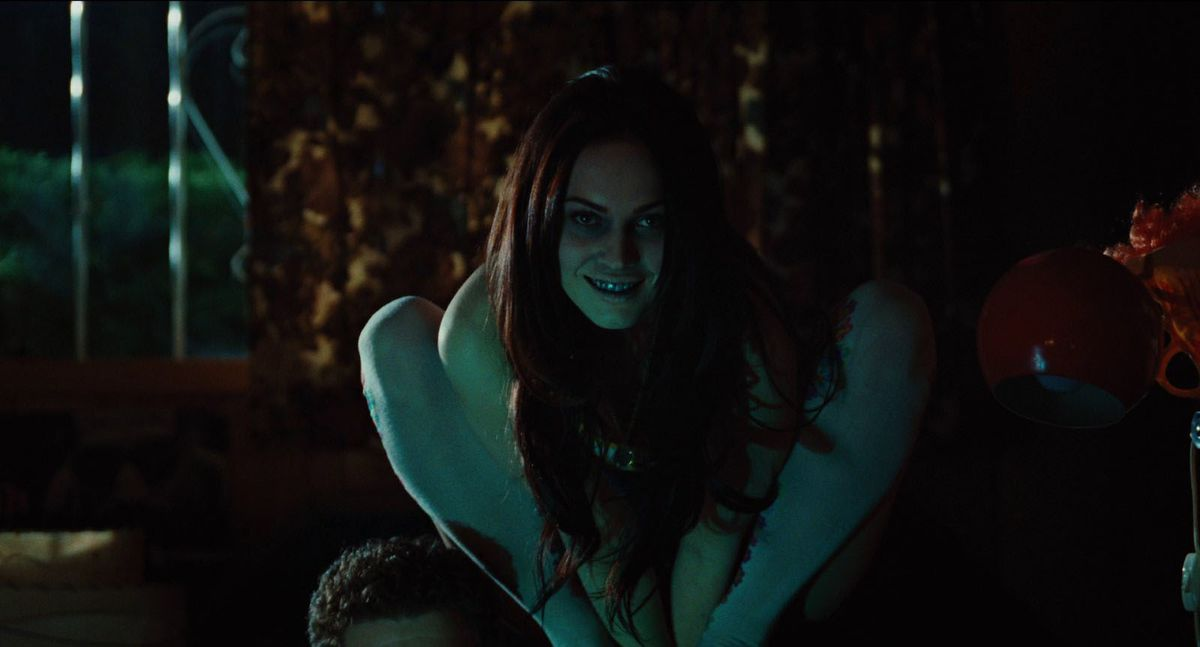 Megan Fox as Jennifer in Jennifer's Body, crouched on top of a chair like a demon out of Henry Fuseli's 1781 painting The Nightmare.