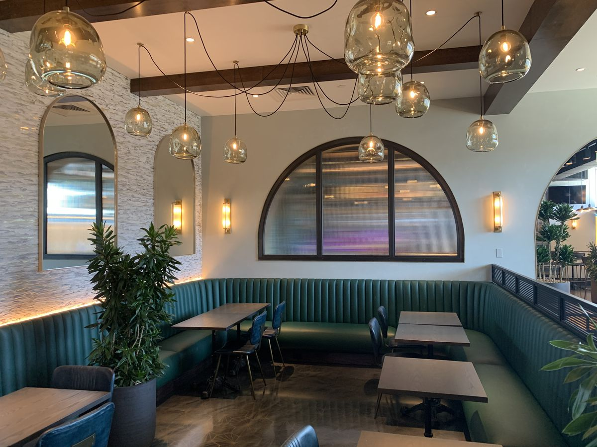 A restaurant dining room adorned with a banquette, leather chairs, and a chandelier that conjures an octopus