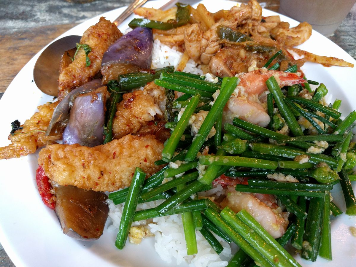 A white plate of food has fish stir-fry, rice, and greens
