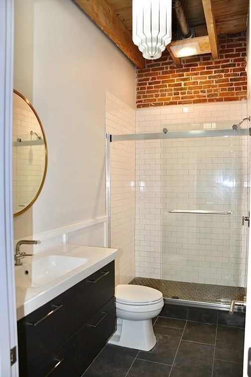 A bathroom with a glass-enclosed shower next to a toilet.