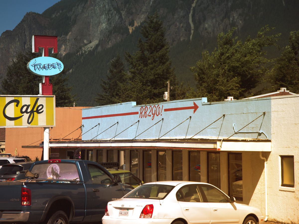 """A short, wide, white building with a long simple awning and parking in the front. A sign has a big red T on top with a blue oval that says """"Twede's"""" on top of a yellow-and-white striped sign that says """"Cafe."""""""