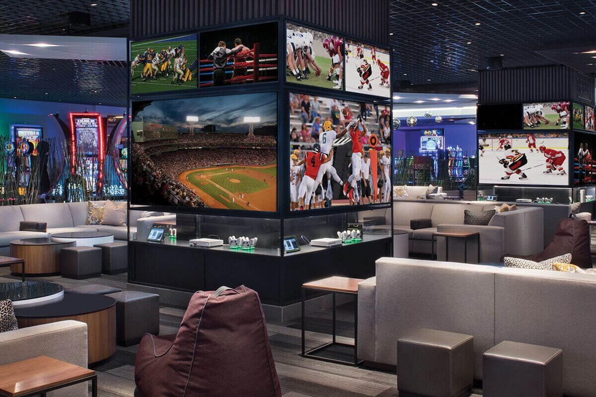 A man cave looking sports book with couches and TVs