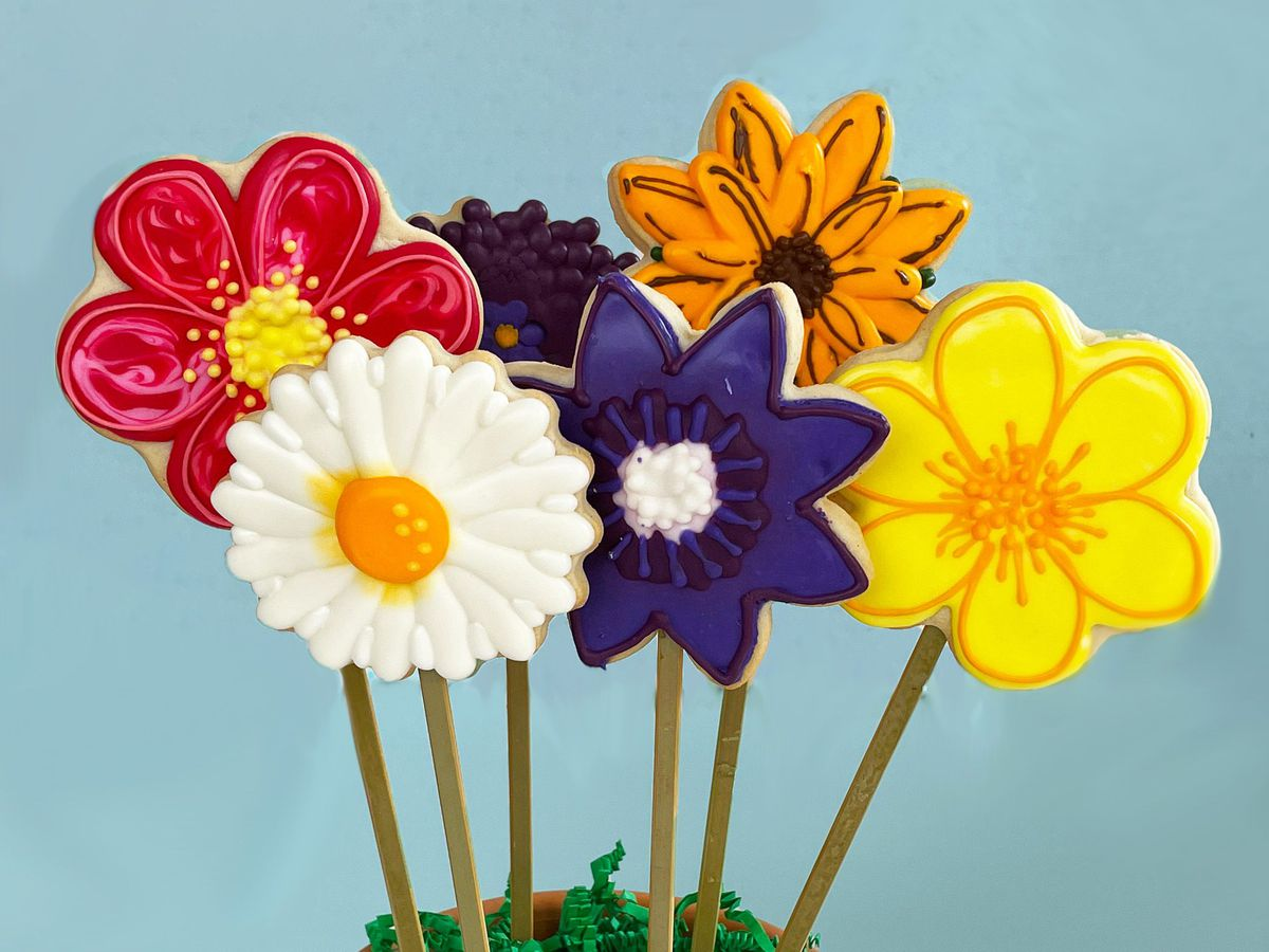 Flower-shaped cookies on sticks stand upright in a flower pot.
