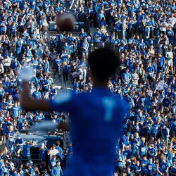 Fans gather as players warm up on the field ahead of an NCAA college football game between BYU and Utah at LaVell Edwards Stadium in Provo on Saturday, Sept. 11, 2021.
