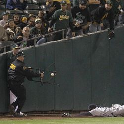 A security guard moves a chair from the path of Seattle Mariners center fielder Trayvon Robinson, right, who cannot make the catch on a ball hit in foul territory by Oakland Athletics' Coco Crisp in the fifth inning of a baseball game Friday, Sept. 28, 2012, in Oakland, Calif.