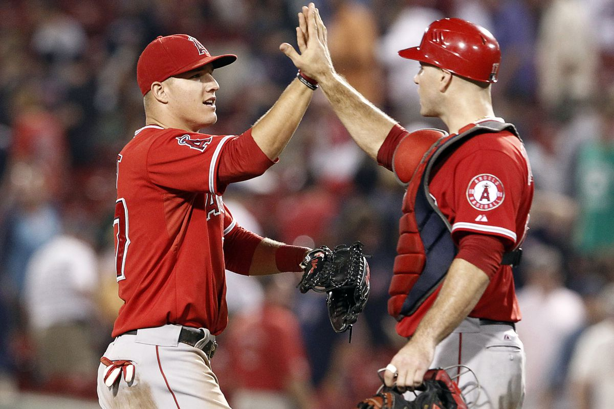 Aug 23, 2012; Boston, MA, USA; Los Angeles Angels center fielder Mike Trout (left) celebrates a victory over the Boston Red Sox with catcher Chris Iannetta (right) at Fenway Park.  Mandatory Credit: Mark L. Baer-US PRESSWIRE