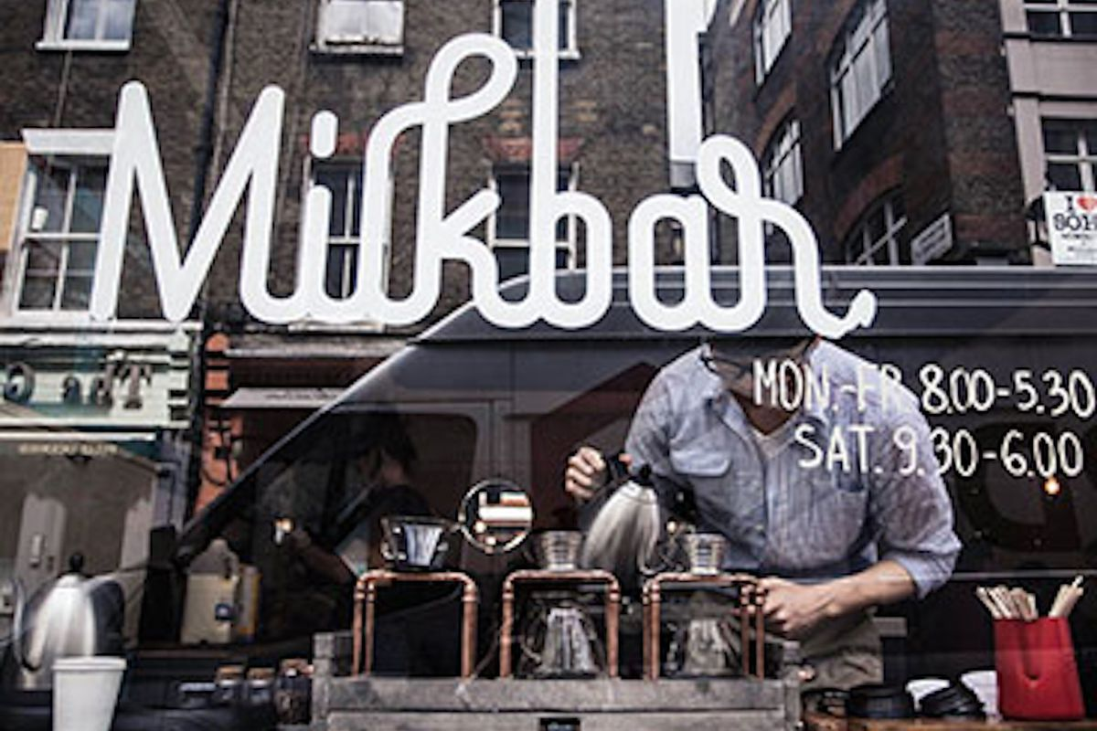 The front of Soho cafe Milkbar, with the logo in the window, and a barista pouring a filter coffee on a Kalita Wave