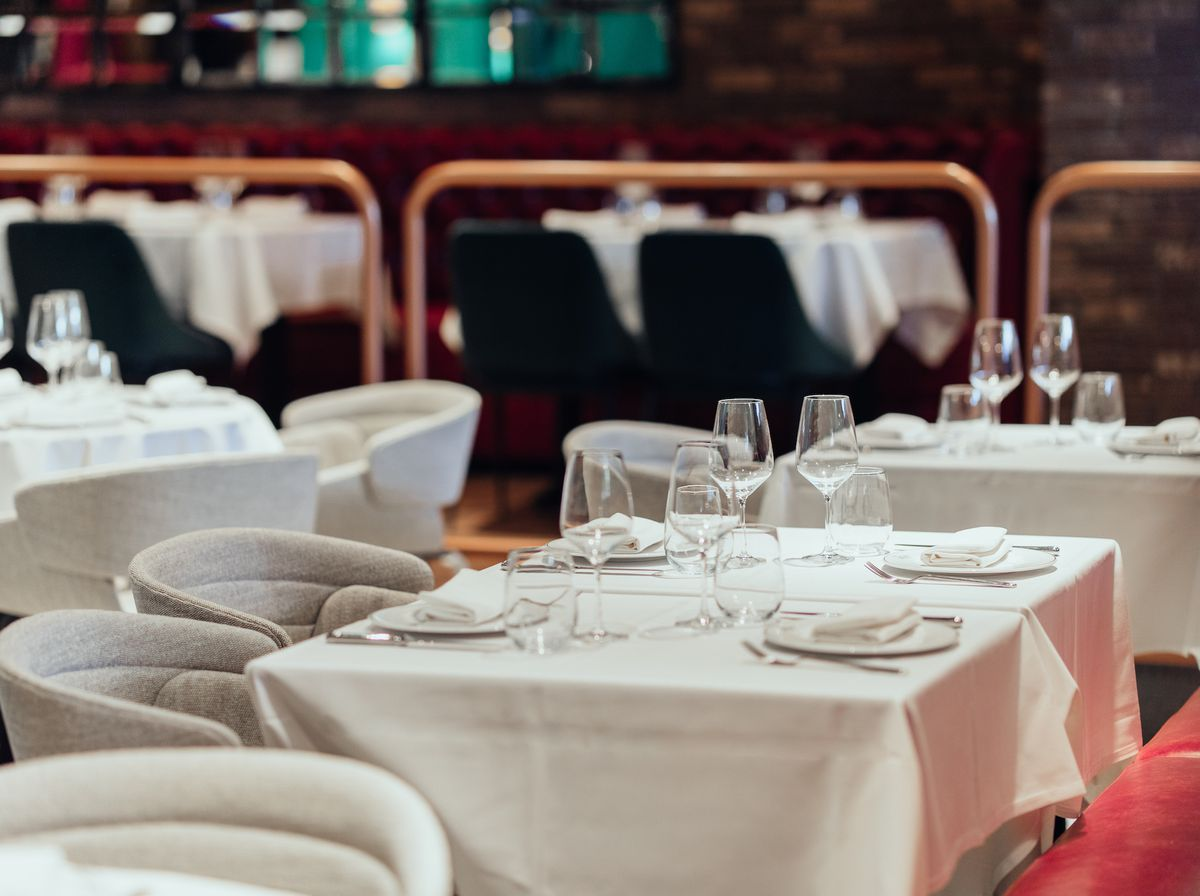 Round-backed chairs and white tablecloths at an upscale new LA restaurant.