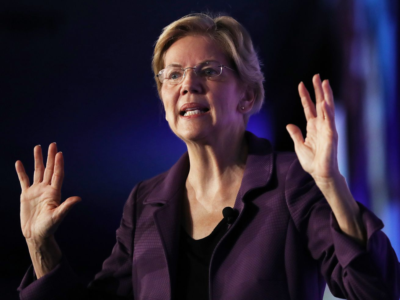 Elizabeth Warren stands on stage with her hands in the air.