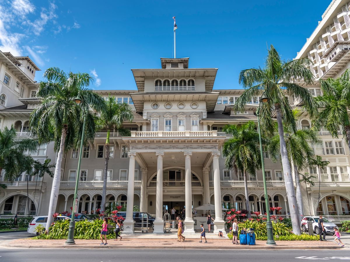 Historic Beaux-Arts hotel with four columns at the entrance. Palm trees surround the property.