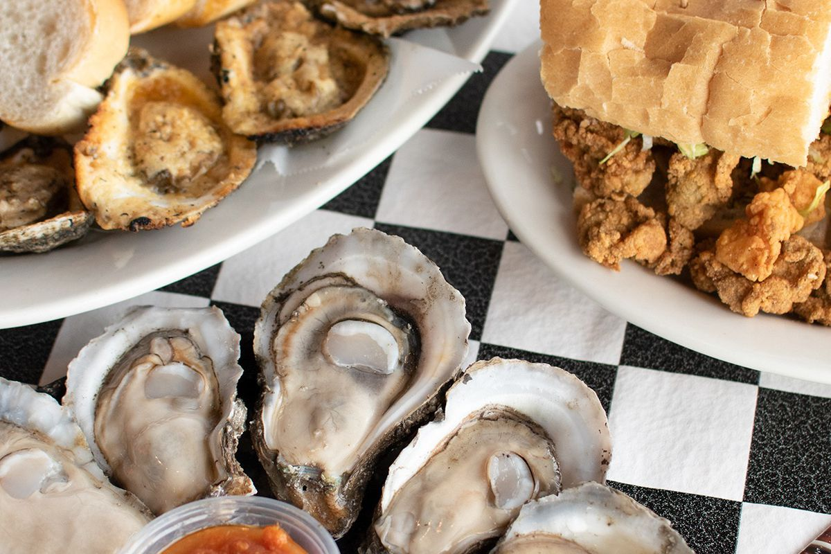 a spread of raw oysters, a po'boy and chargrilled oysters on a checkered tablecloth