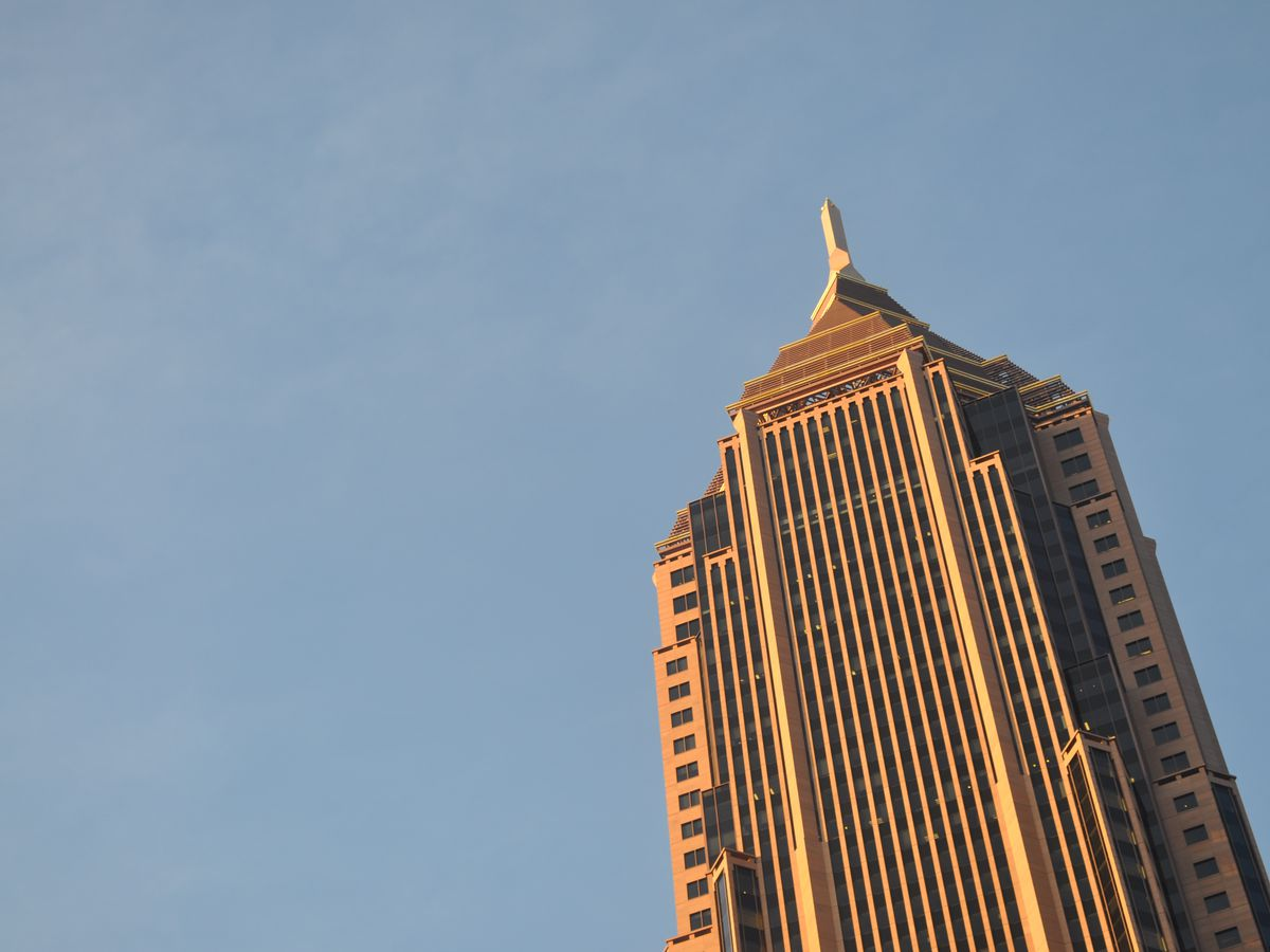 The top of a tall skyscraper. The facade is gold colored.