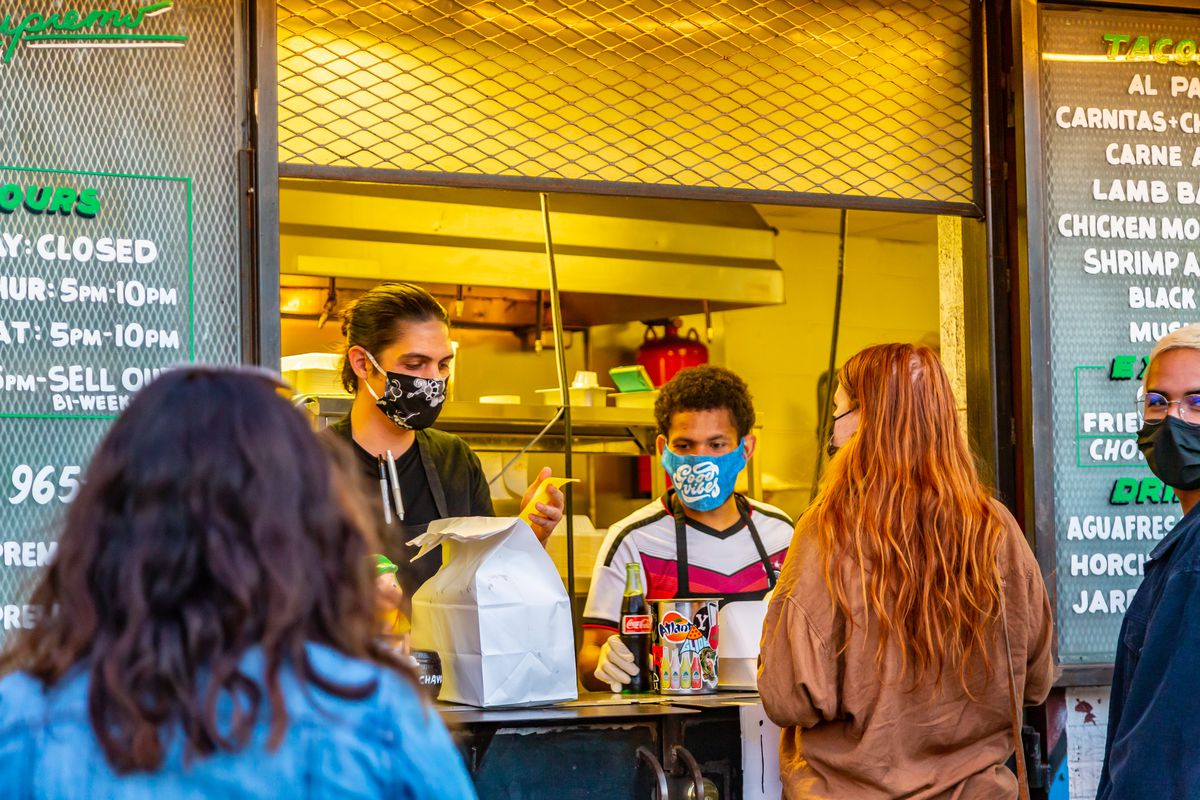 Three friends in masks standing at the to-go window at Supremo Taco in Grant Park, Atlanta, picking up their orders. A young person of African-American descent in a black mask with blonde hair and in gold rimmed glasses stares at the camera with smiling eyes. Two masked staff workers bag up the orders
