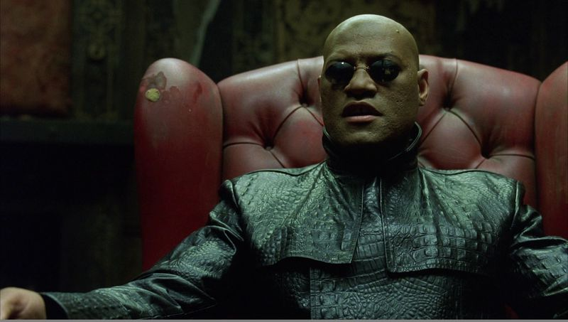 Morpheus wearing sunglasses and sitting in a red chair