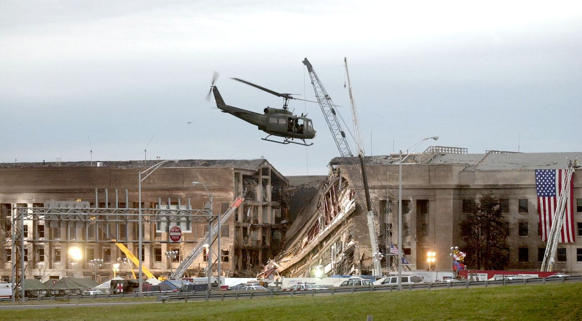A military helicopter flies in front of the Pentagon on September 14, 2001 in Arlington, Virginia at the impact site where a hijacked airliner crashed into the building.