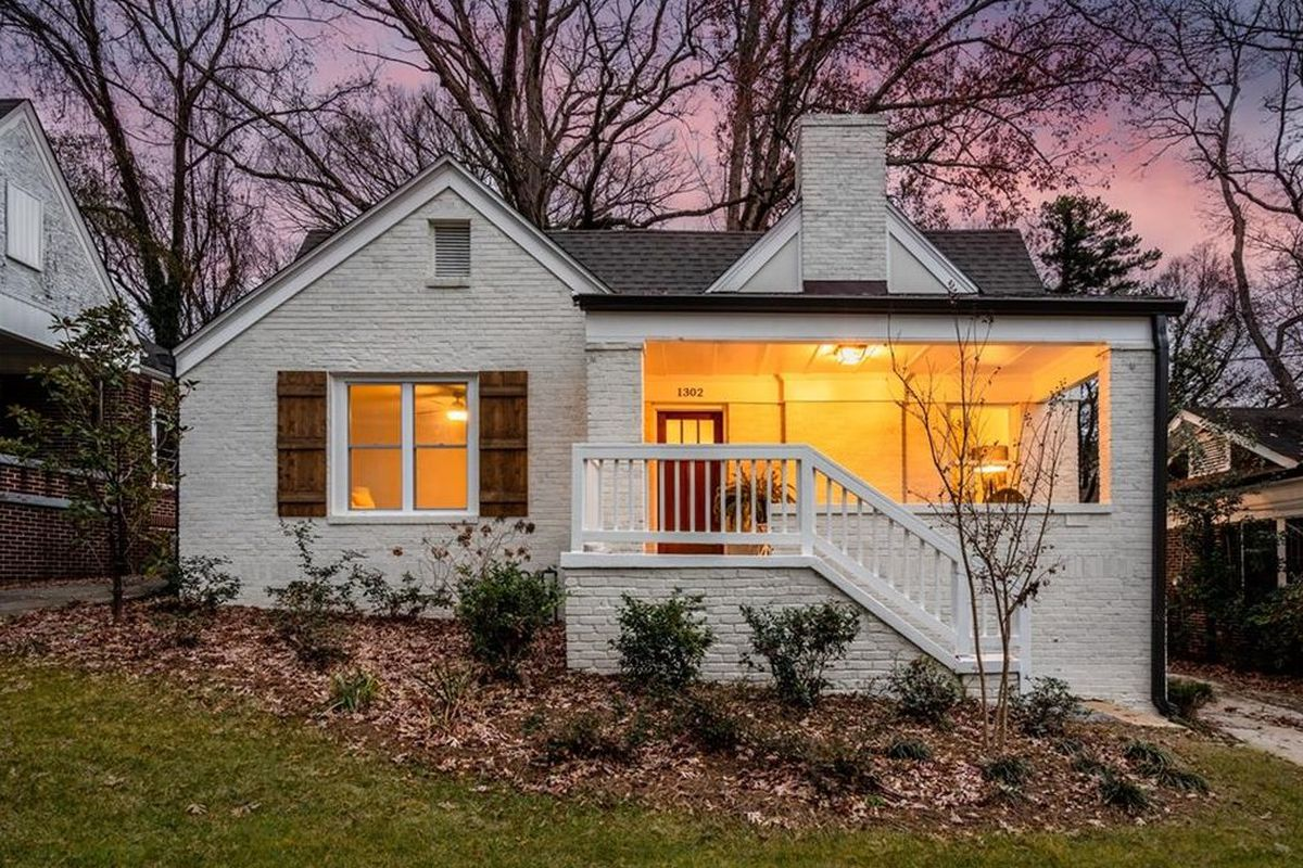 A white cottage with a large front porch and brown shutters with a pink sunset in the background.