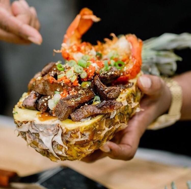 A black hand holds a half of a pineapple filled with teriyaki chicken with a shrimp placed near the pineapple's leaves