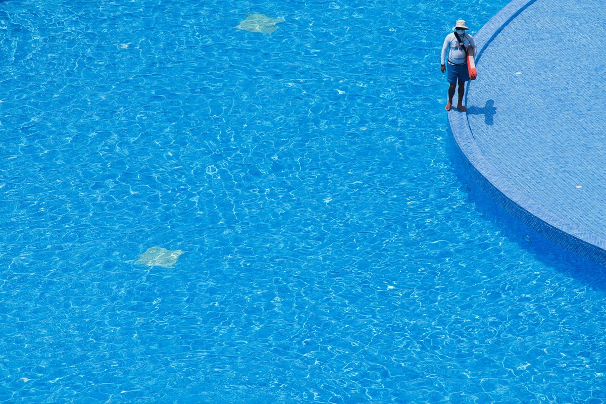 A lifeguard stands at a pool in Dubai.