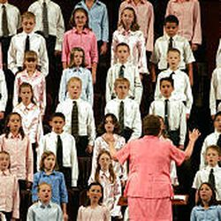 Jane Knudsen Poulsen directs the Primary Choir from stakes in the West Jordan area on Saturday afternoon.