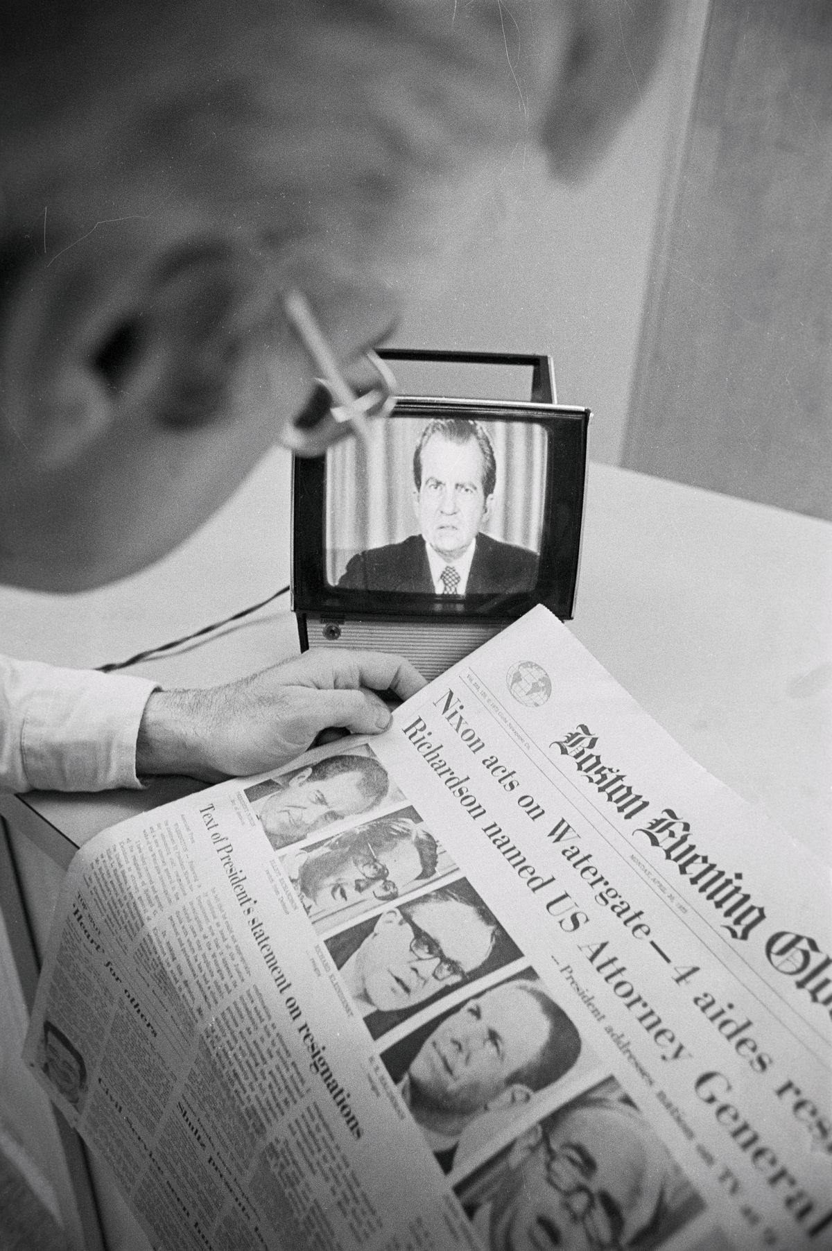 A man is looking at a copy of the Boston Evening Globe newspaper about Watergate while also watching President Nixon on a small television screen.