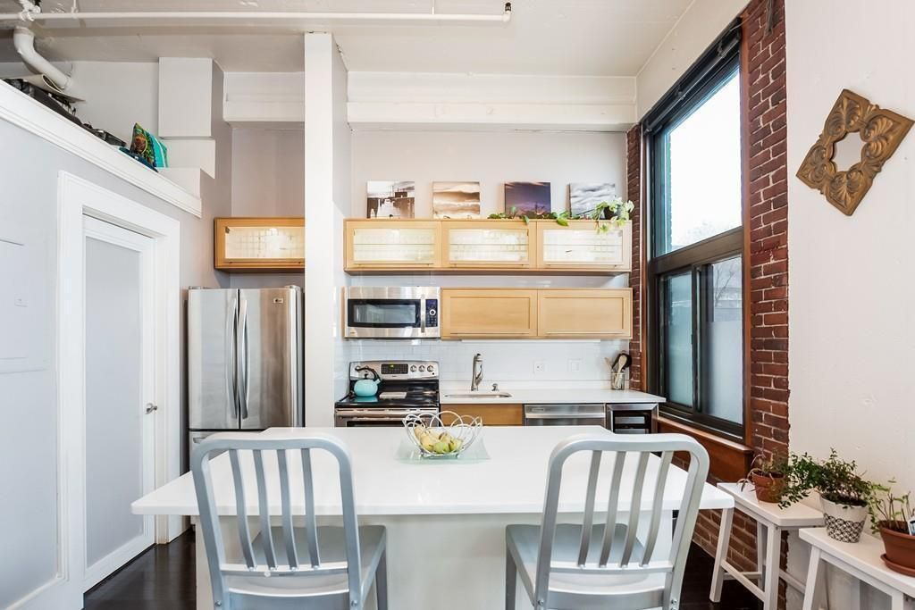 A view of the kitchen over two chairs and a countertop.