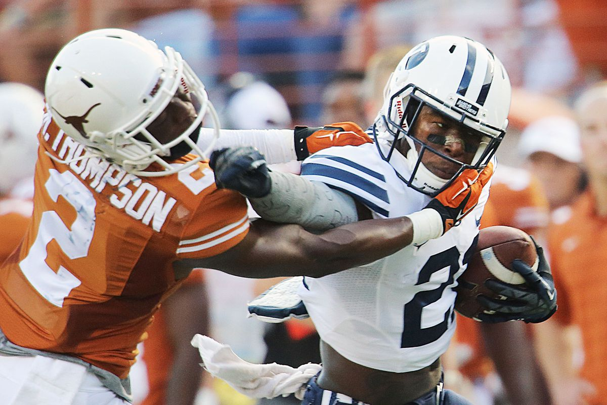 BYU's Jamaal Williams battles to get away from Mykkele Thompson Saturday in Austin, Texas.