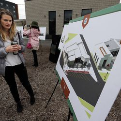 Suzanne Gillis looks at renderings during a groundbreaking for the new Central Ninth Market in Salt Lake City, Wednesday, Oct. 28, 2015. The 9,216-square-foot commercial building will be occupied by six locally-owned small businesses, including Jade Market, which will stand as the first local food market in the neighborhood.