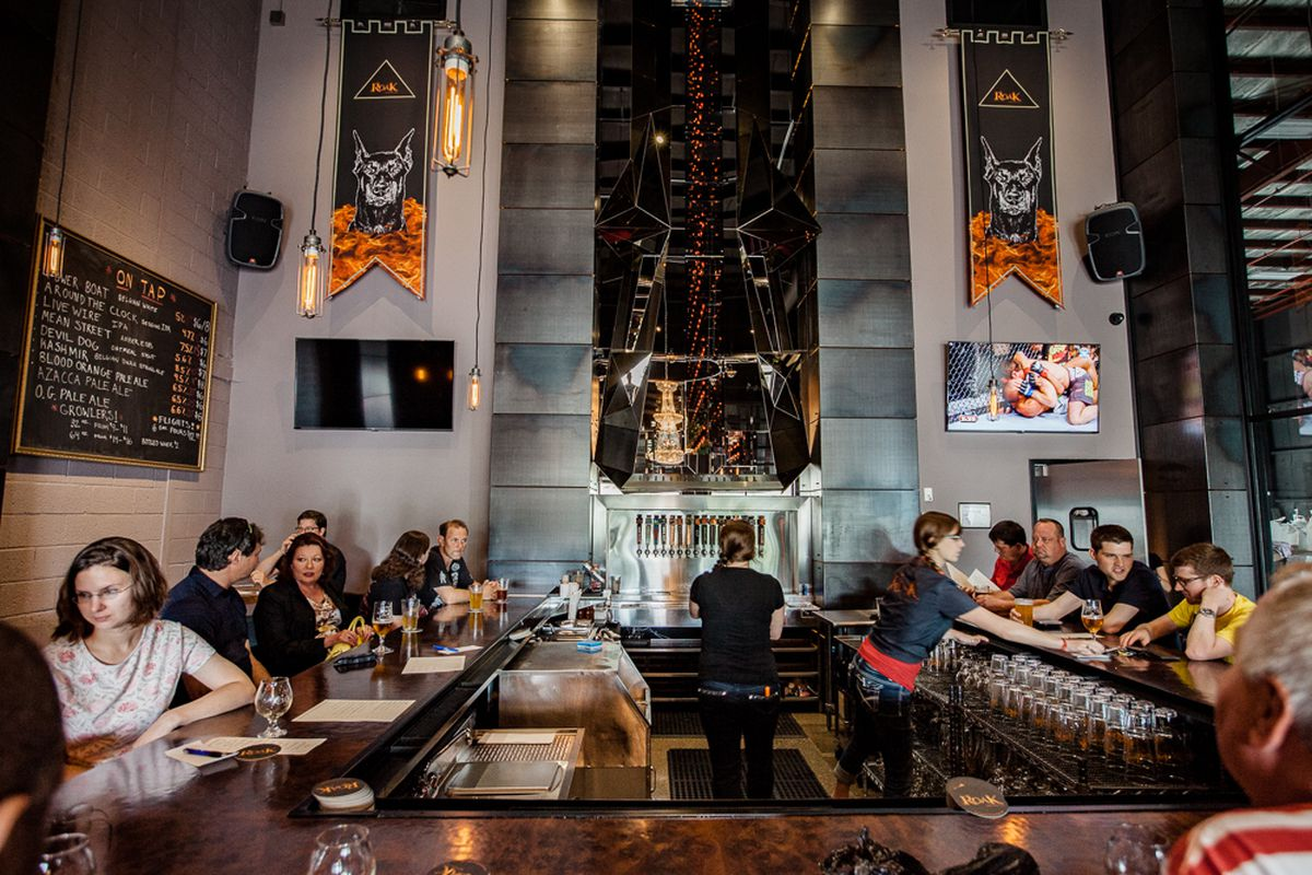 The interior of the Roak Brewing Company taproom is filled with people at a U-shaped bar.