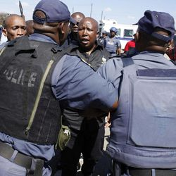 Firebrand politician Julius Malema, centre, argues with police officers, at Lonmin Platinum Mine near Rustenburg, South Africa, Monday, Sept. 17, 2012. London-registered Lonmin PLC announced it is halting construction of a new shaft, putting 1,200 people out of work, as the bloody and bitter strike at its beleaguered South African platinum mine dragged on its fifth week. The strikes that have halted work at seven gold and platinum mines have spread to the chrome sector, according to the official South African Press Association. Meanwhile, police blocked rabblerousing politician Julius Malema from addressing some 3,000 strikers gathered at a stadium at the Lonmin mine at Marikana, northwest of Johannesburg.