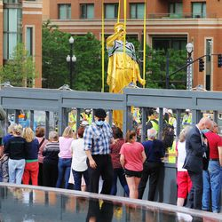 Onlookers gather at the fence to get a closer look of the Angel Moroni statue after workers from Jacobsen Construction removed it from the Salt Lake Temple of The Church of Jesus Christ of Latter-day Saints in Salt Lake City on Monday, May 18, 2020.