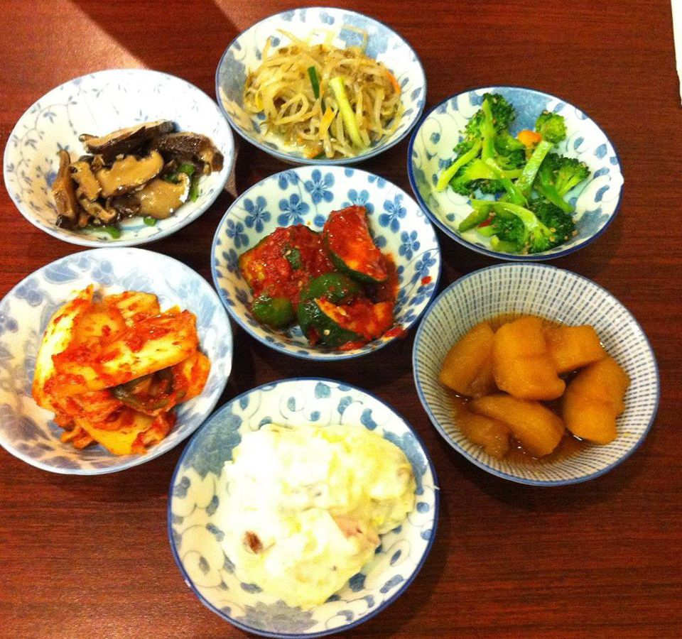 assorted banchan in scattered bowls, on red surface