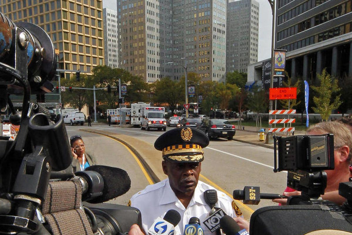 Pittsburgh Police Chief Nate Harper, center, briefs media outside the 3 Gateway Center building, rear center, in downtown Pittsburgh, Friday, Sept. 21, 2012. Police are trying to negotiate with a man claiming to have a bomb and a gun on the 16th floor of