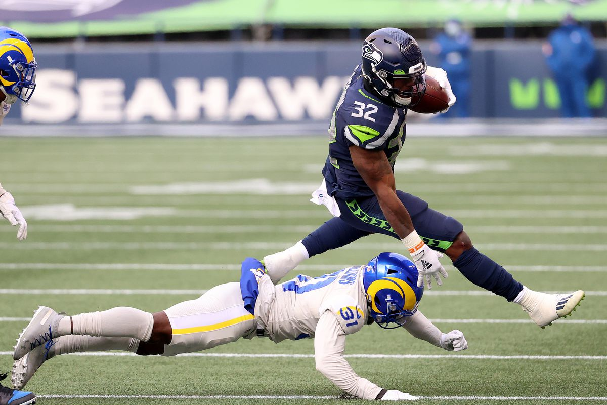 Chris Carson #32 of the Seattle Seahawks is tackled by Darious Williams #31 of the Los Angeles Rams during the second quarter at Lumen Field on December 27, 2020 in Seattle, Washington.